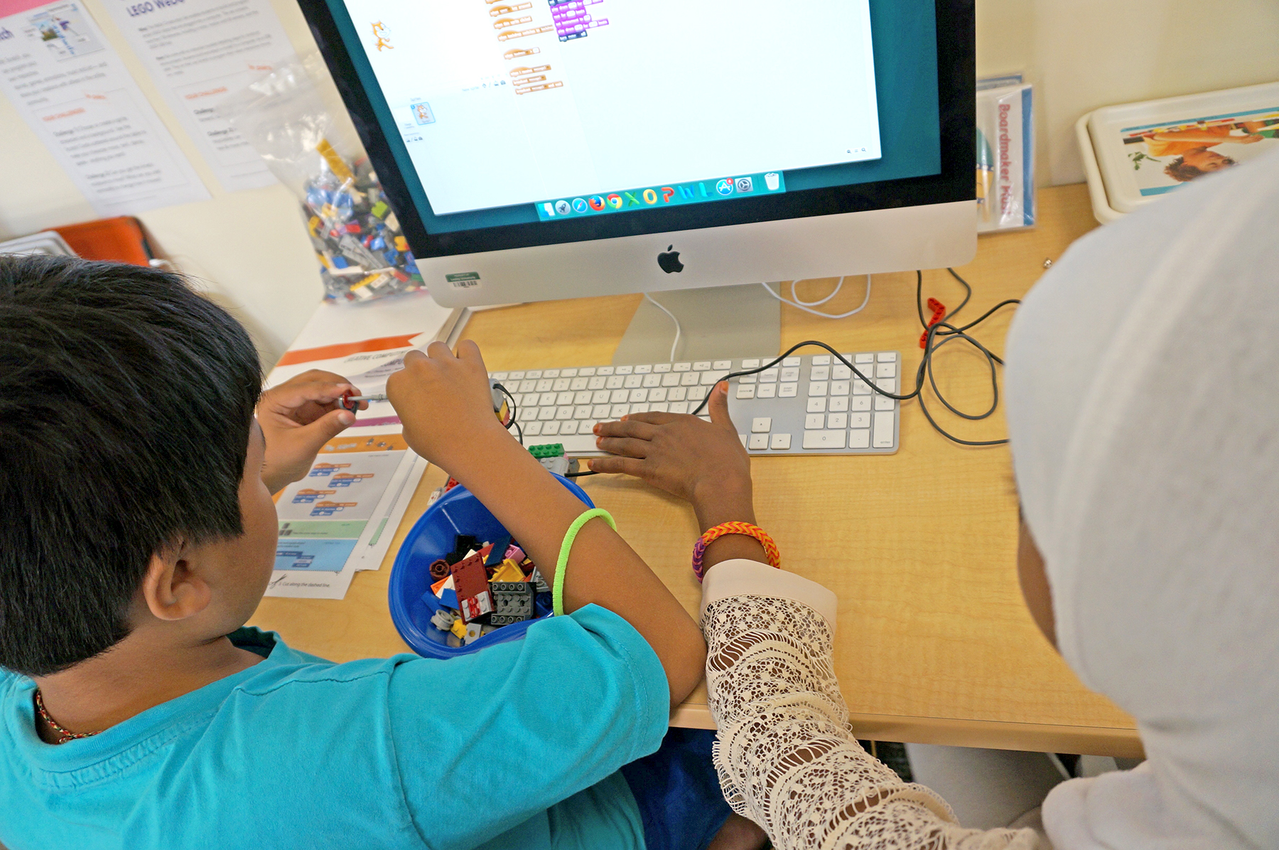 Two students engage with Scratch and Lego Wedo robotics at computer terminal