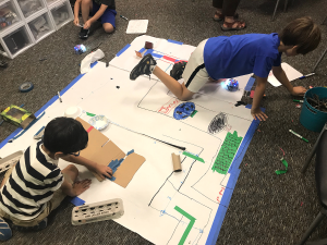 Wonderlab students engaged in making: using BeeBots, recyclables, and natural materials to design their own forrest pathways