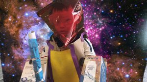 Student dressed in handmade space costume stands in front of a galaxy using the GreenScreen app by DoInk.